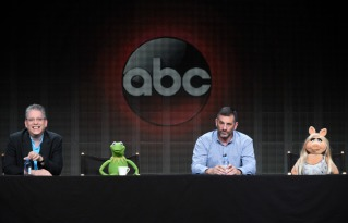 "Writer/executive producer Bill Prady, from left, Kermit the Frog, writer/executive producer Bob Kushell and Miss Piggy participate in ""The Muppets"" panel at the Disney/ABC Summer TCA Tour. (Photo by Richard Shotwell/Invision/AP)"