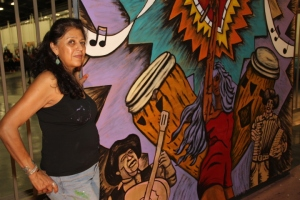Visual Artist Pola Lopez next to 8' x 8' mural she painted live